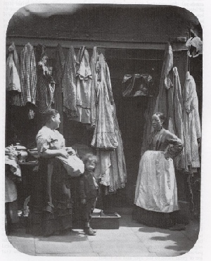Two Women Stand Talking Outside A Used Clothing In St Giles