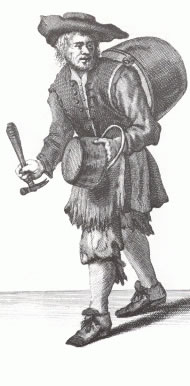 A ragged tinman, carrying pots and pans is shown walking towards the viewer